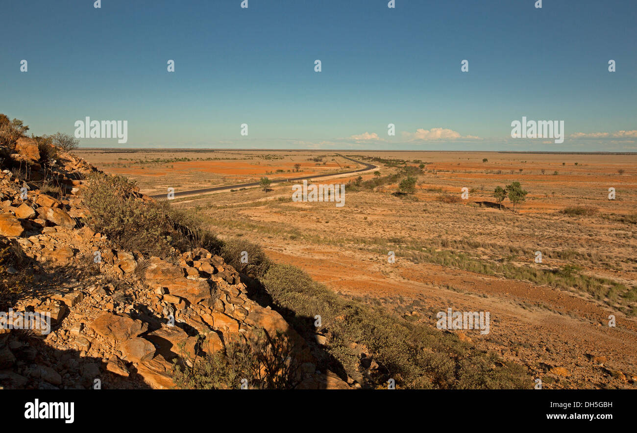 Vast barren Australian outback landscape with road slicing across treeless plains stretching to distant horizon in western Queensland during drought - Stock Image