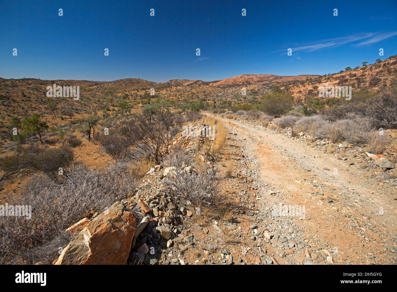 Stony outback track through rocky hills of East MacDonnell Ranges near Alice Springs Northern Territory Australia - Stock Image