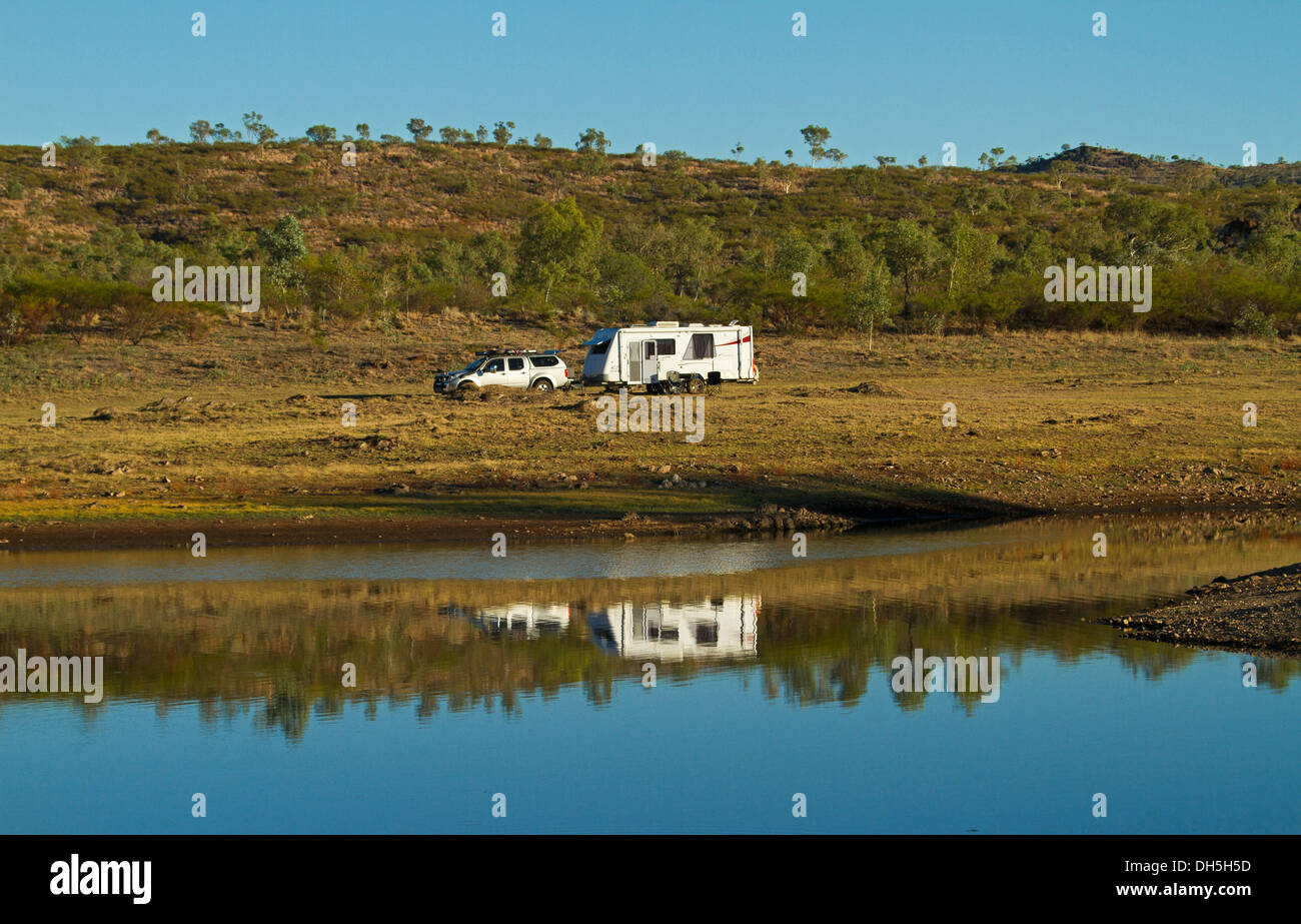 White caravan and car / four wheel drive vehicle parked on grassy hill reflected in blue water - Lake Corella outback Queensland - Stock Image