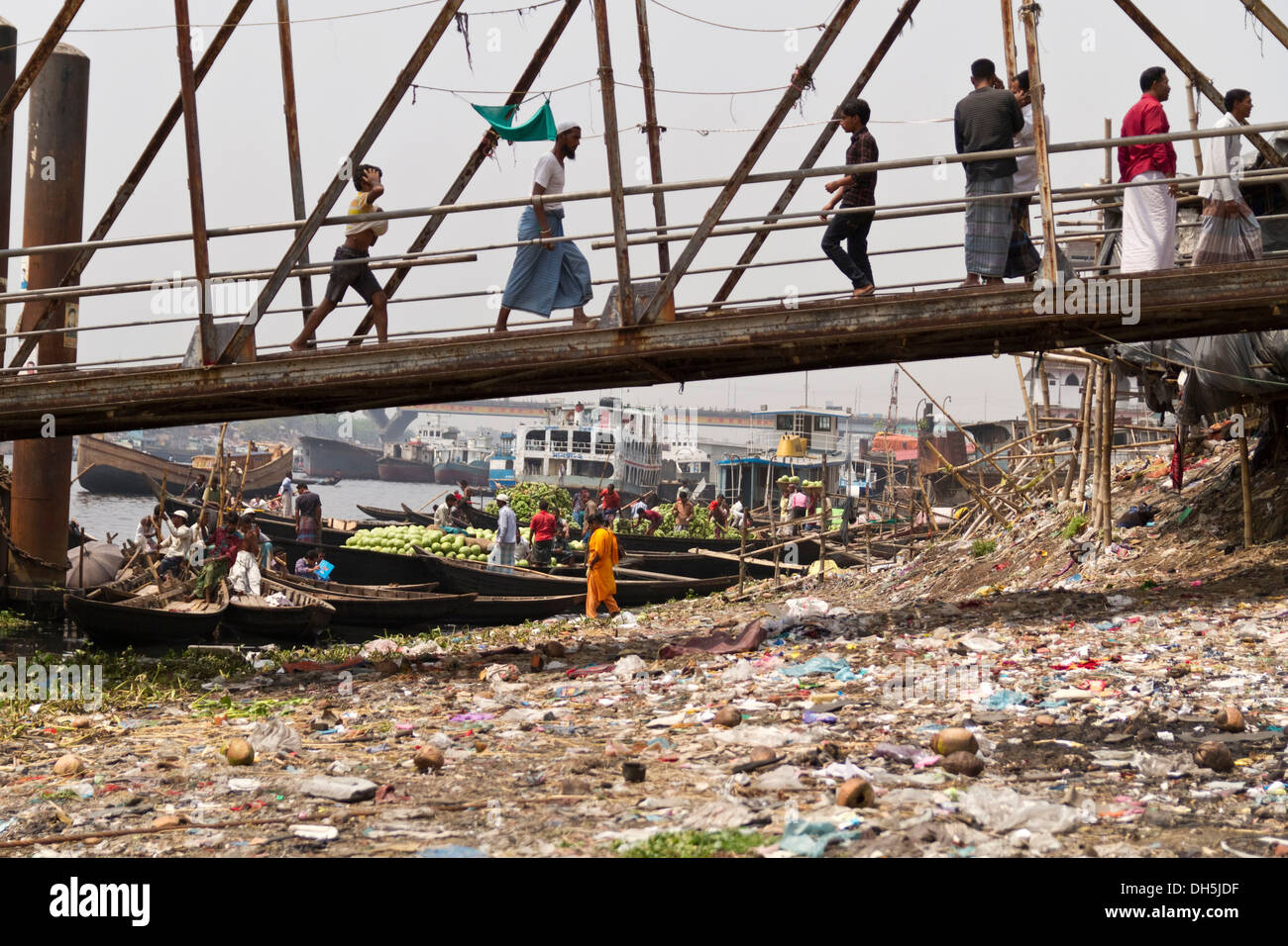 Bank of the Buriganga River, rubbish-filled shore, pedestrians crossing over a bridge to the ferry terminal, Dhaka, Bangladesh - Stock Image