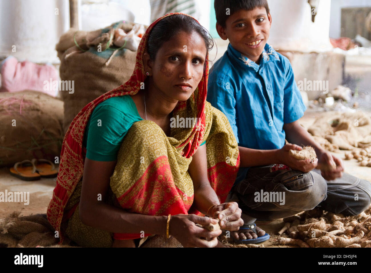 Woman and a boy sorting roots, spice market, Old Dhaka, Dhaka, Bangladesh, South Asia - Stock Image