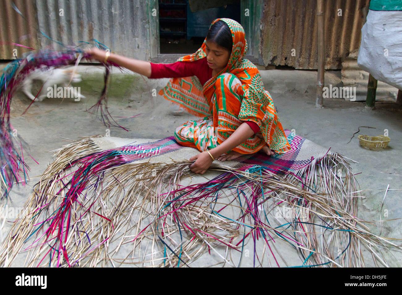 Young woman weaving raffia in front of a tin-sheet home, Barakandi, Sirajganj, Bangladesh, South Asia - Stock Image