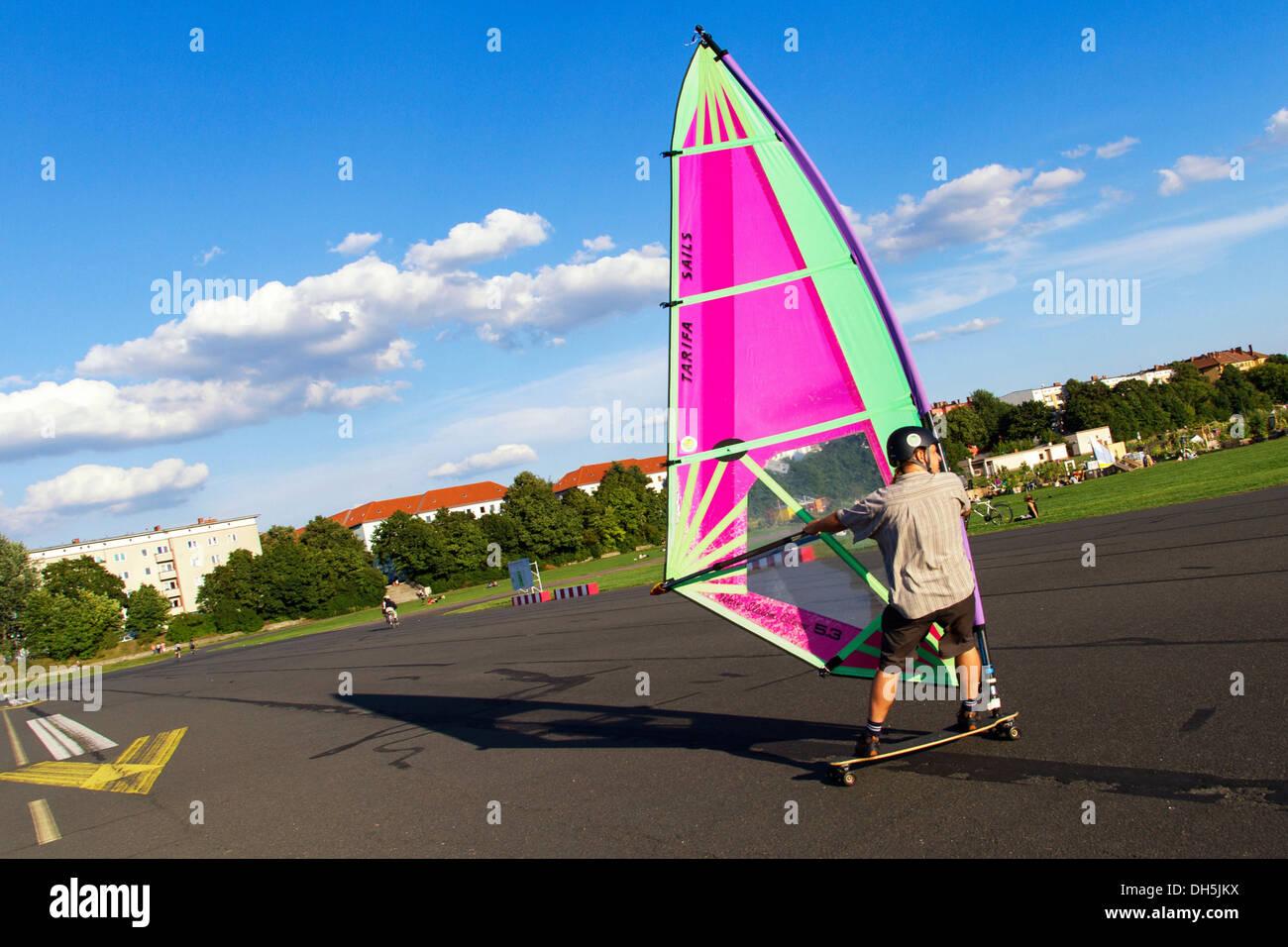 Windskater practicing on the asphalt runway with a windsurfer sail and a longboard, Berlin-Tempelhof, Tempelhofer Feld, Berlin - Stock Image