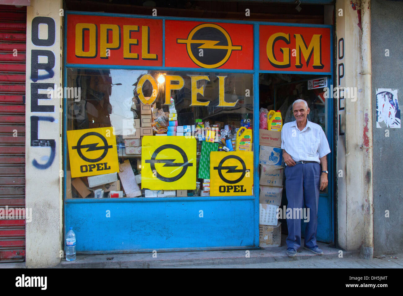 Old man is standing at a shop entrance, shop selling spare parts for ...