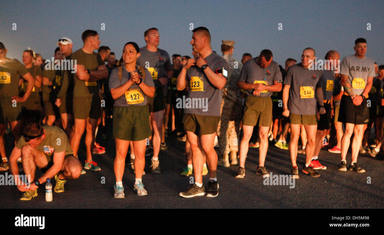 Runners stretch prior to the start of the 2013 Marine Corps Marathon Forward at Camp Leatherneck, Afghanistan Oct. 27. More than 300 runners participated in this year's marathon. This is the fifth year a satellite marathon has been held at Camp Leathernec - Stock Image