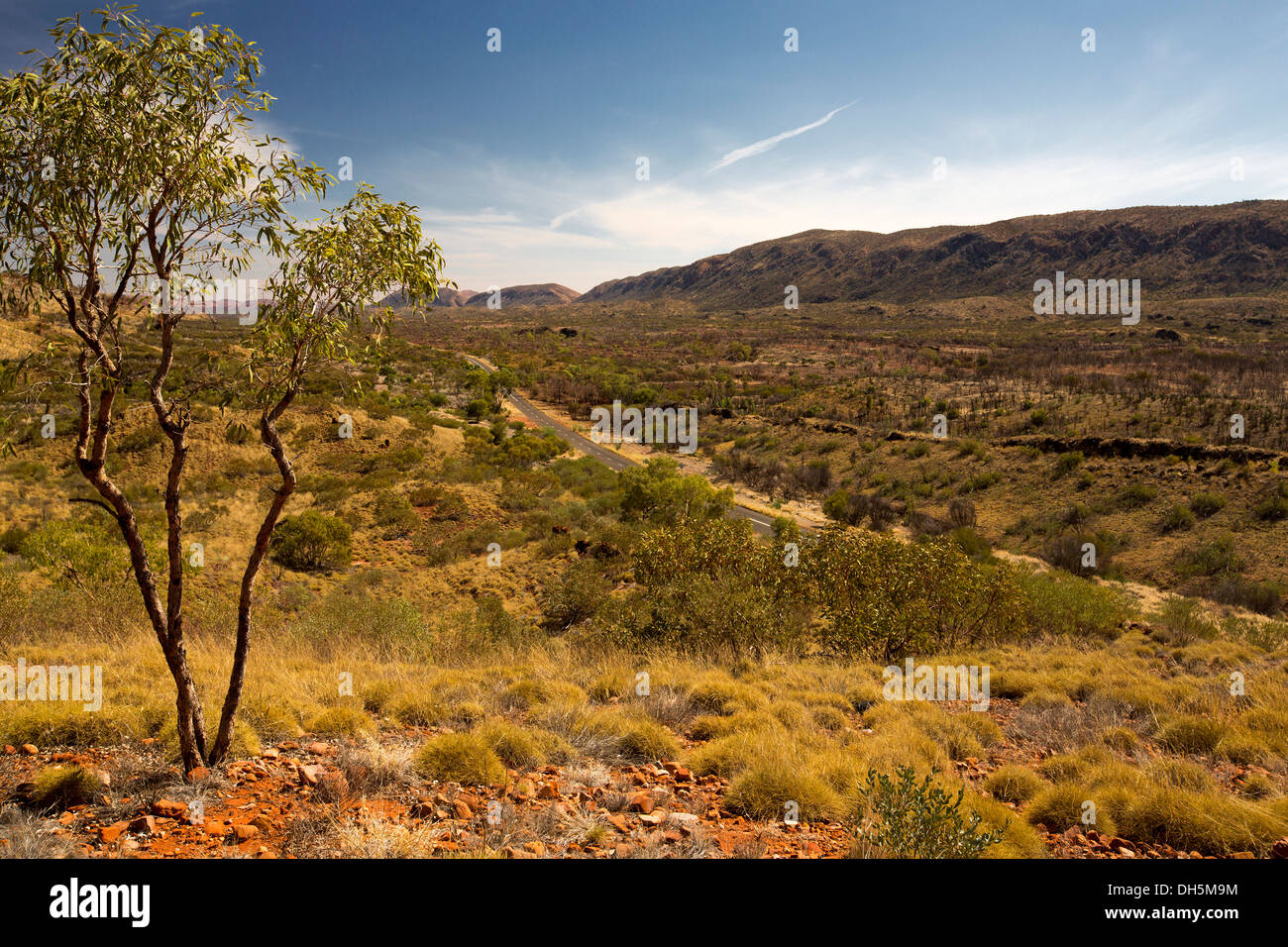 View of vast outback landscape, road, and West MacDonnell Ranges from lookout near Alice Springs in Northern Territory Australia - Stock Image