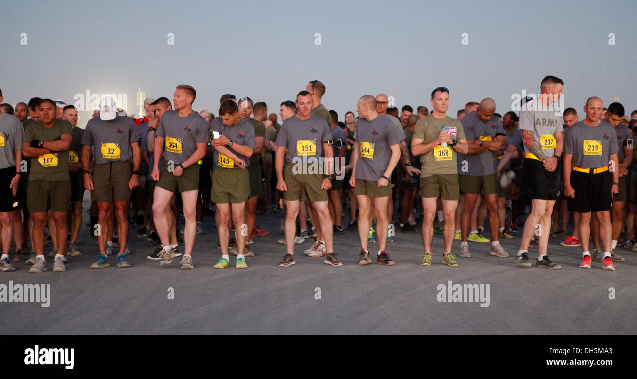 Runners stretch prior to the start of the 2013 Marine Corps Marathon Fowrard at Camp Leatherneck, Afghanistan Oct. 27. More than 300 runners participated in this years marathon. This is the fifth year a satellite marathon has been held at Camp Leatherneck - Stock Image