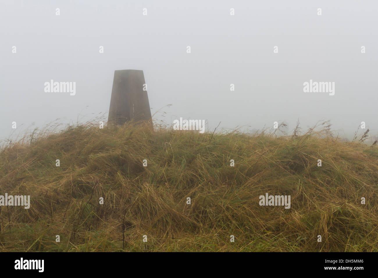 In low lying cloud, triangulation Point on Eggardon Hill, Dorset, England, United Kingdom. - Stock Image