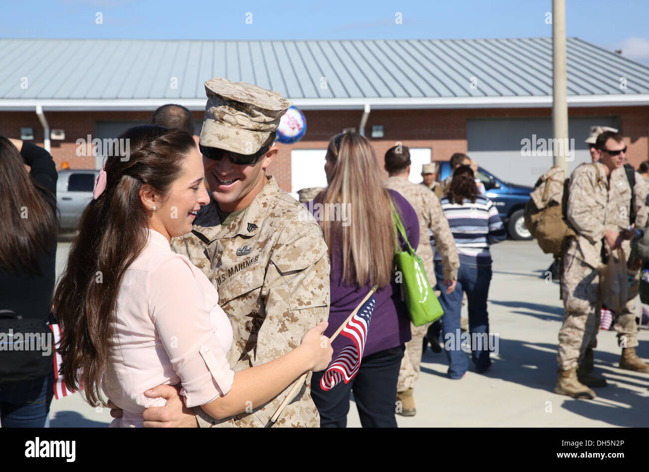 A Marine with 2nd Explosives Ordnance Disposal Company, 8th Engineer Support Battalion, 2nd Marine Logistics Group reunites with a loved one during a homecoming event for 2nd EOD Co. aboard Camp Lejeune, N.C., Oct. 26, 2013. Service members with the compa - Stock Image