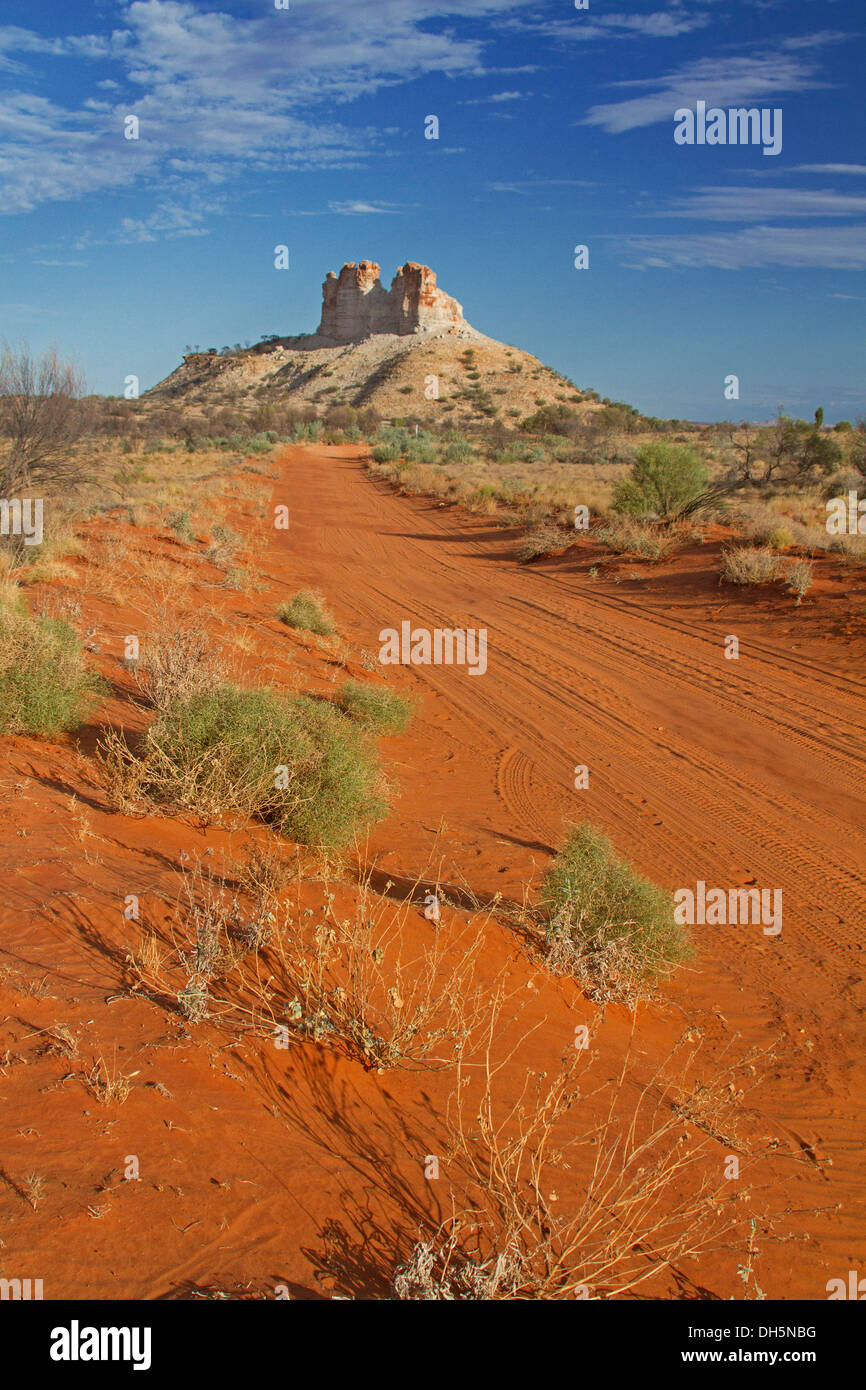 Outback landscape with long red road crossing plains to Castle Rock, unique geological feature in Northern Territory Australia - Stock Image