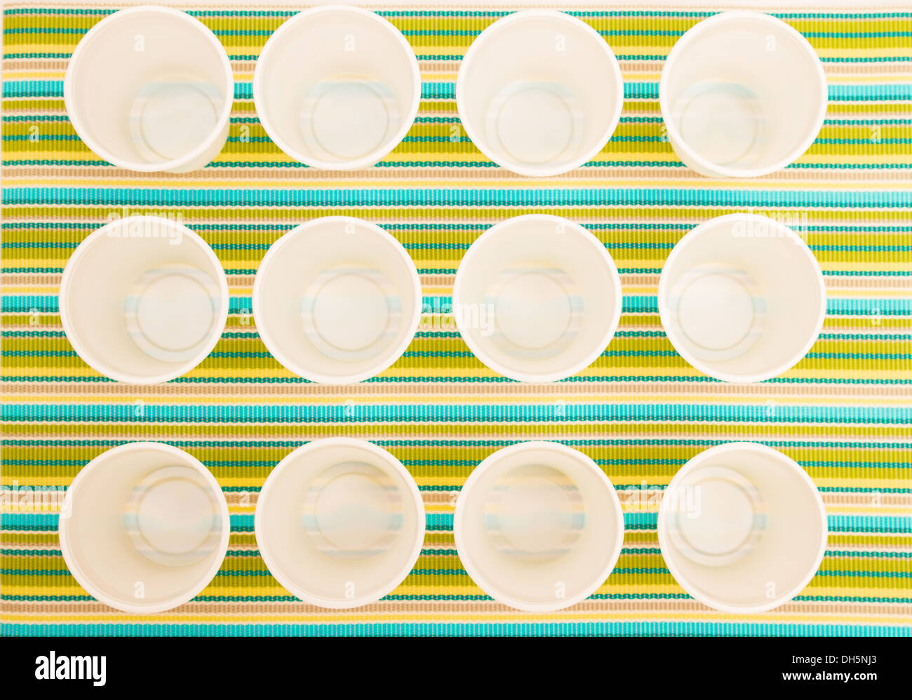 Lots of disposable cups on a colorful background - Stock Image
