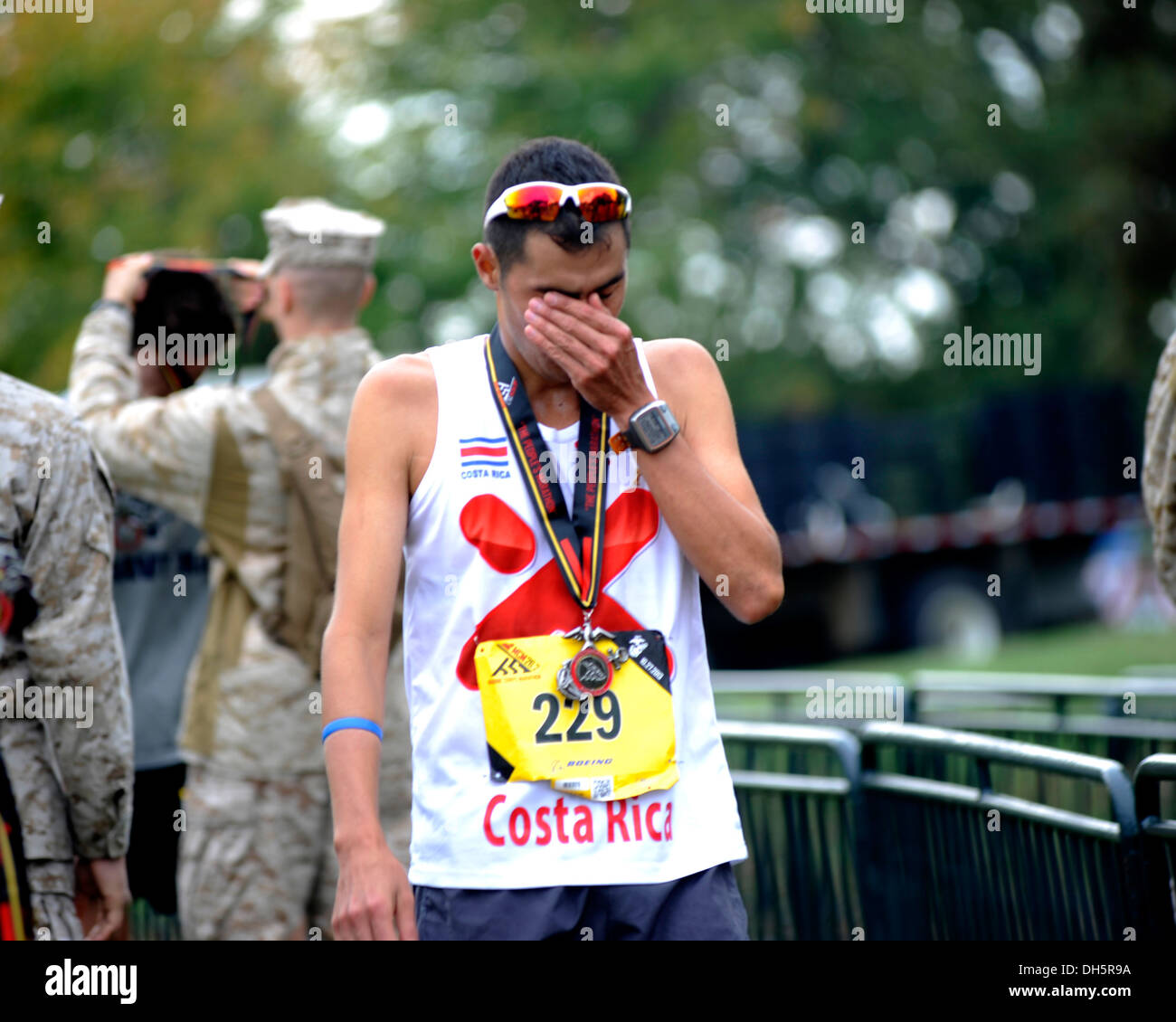 Felix Murillo, a runner in the 38th Annual Marine Corps Marathon, displays emotion upon his completion of running 26.2 miles, Washington D.C., Oct. 27, 2013. Known as 'The People's Marathon,' the 26.2 mile race, rated the 3rd largest marathon in the Unite - Stock Image
