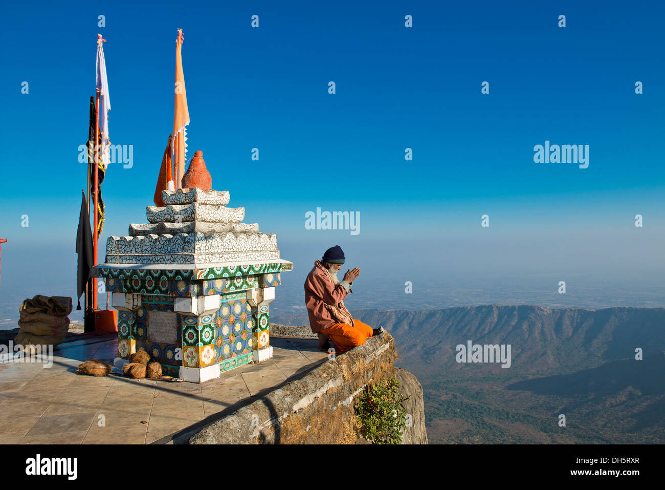 Sadhu or holy man sitting with his hands folded in prayer on the precipice in front of a Hindu temple shrine with Stock Photo