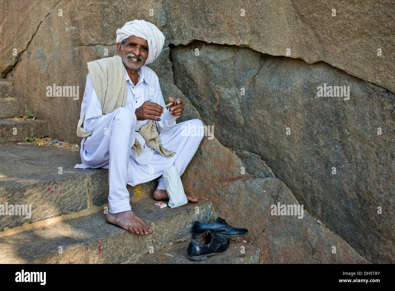 A pilgrim dressed in white is sitting on the stairs leading up to the temple on the holy mountain of Girnar, Junagadh, Stock Photo