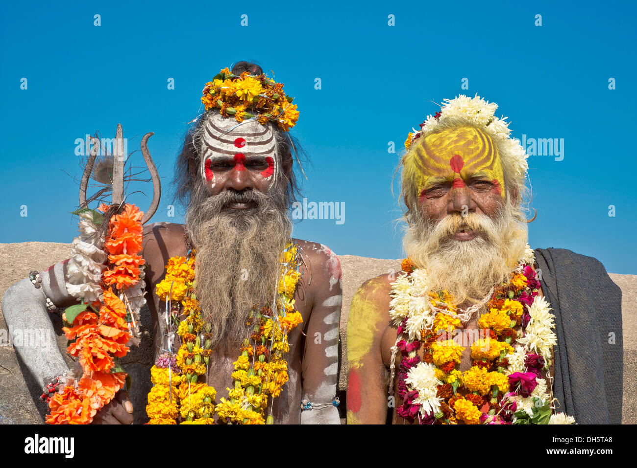 Two sadhus, holy men with a typical face painting, one holding a Trishula trident, Orchha, Madhya Pradesh, India - Stock Image