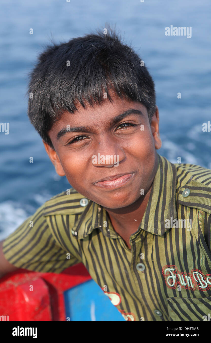 Son of fisherman in the boat off the coast, Varkala, Kerala, India, Asia - Stock Image