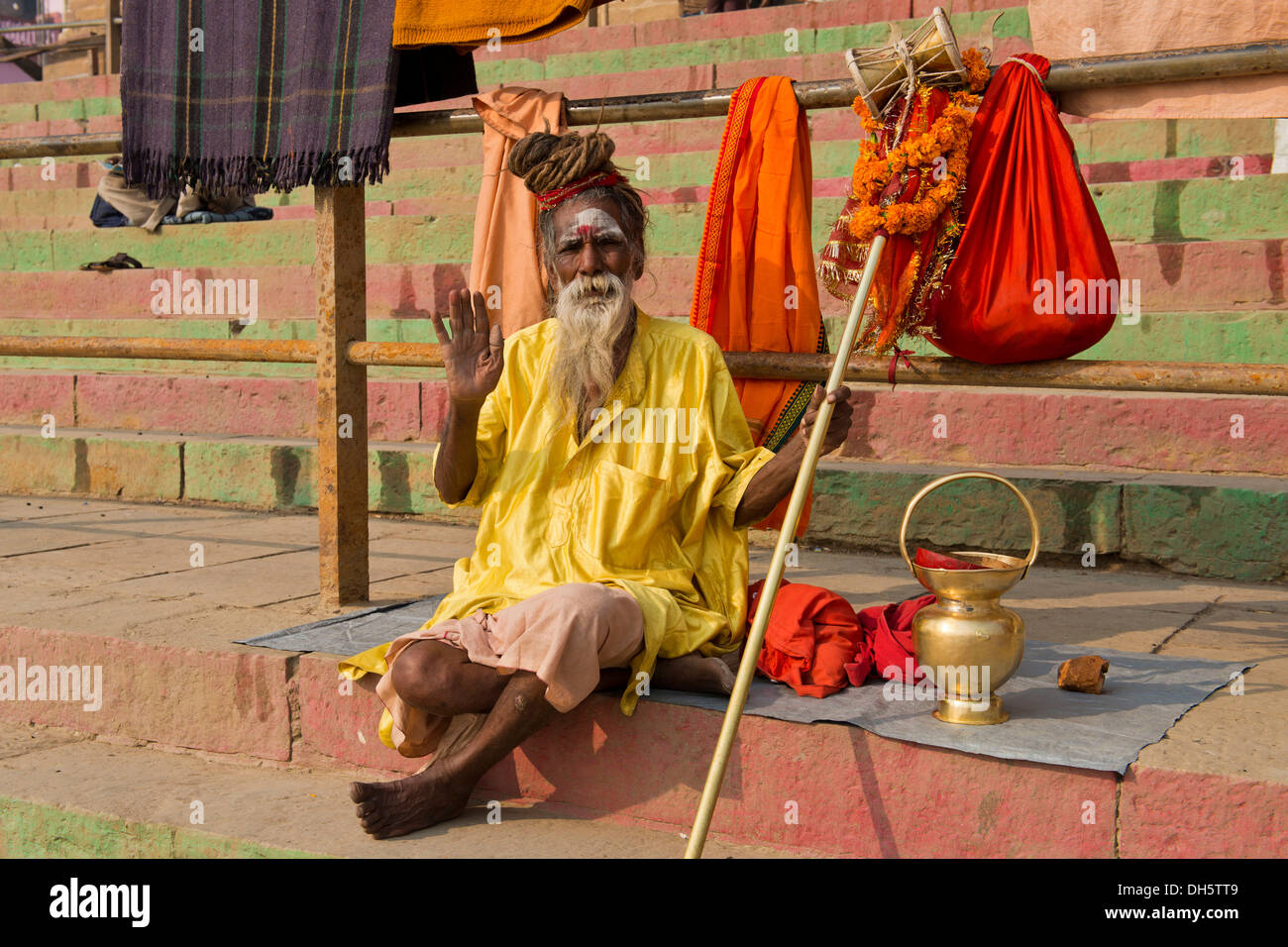 Elderly Sadhu, holy man or wandering ascetic sitting on a blanket on the steps on the bank of the Ganges River with various - Stock Image