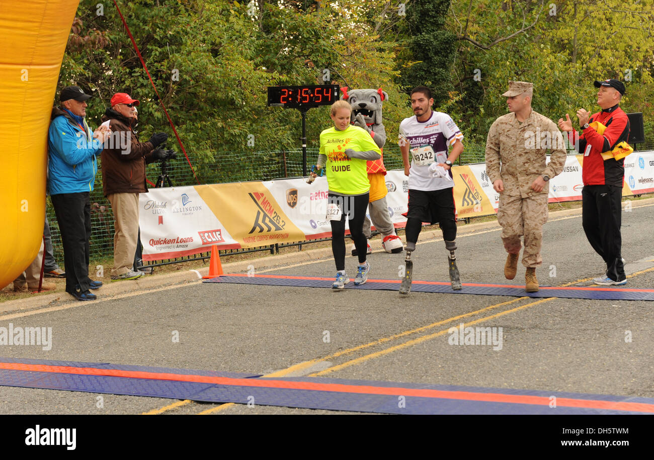 A participant crosses the finish line of the 38th Annual Marine Corps Marathon as supporters and event volunteers cheer him on. - Stock Image