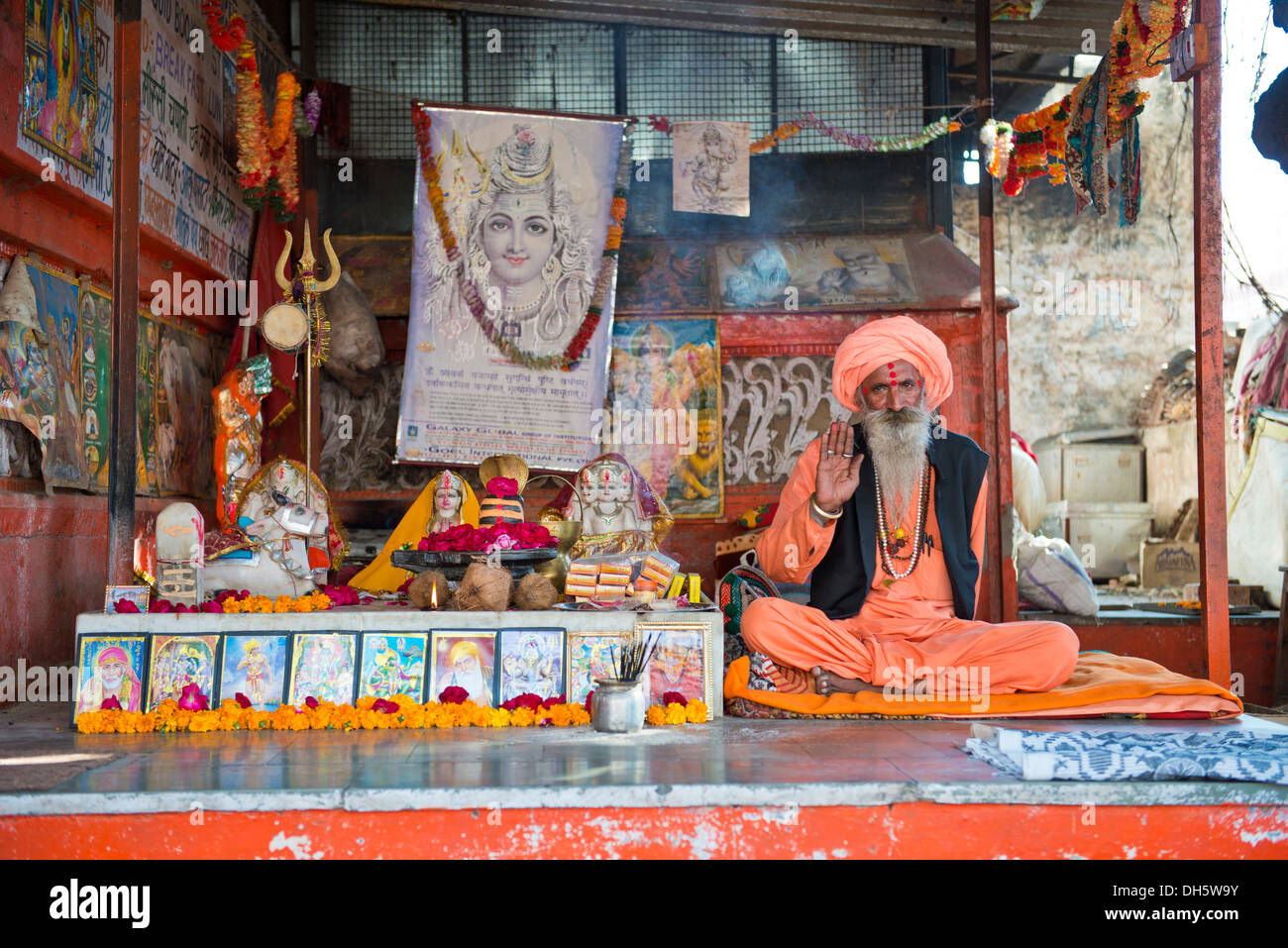 Sadhu, a holy man or wandering ascetic sitting in the lotus position on a mat in a Hindu prayer shrine, Pushkar, Rajasthan - Stock Image
