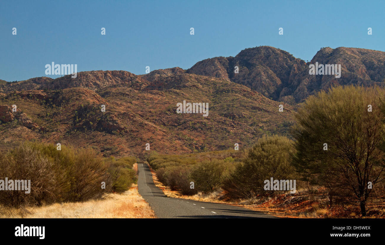 Road in outback Australia bordered by low trees heading towards West MacDonnell Ranges near Alice Springs Northern Territory - Stock Image