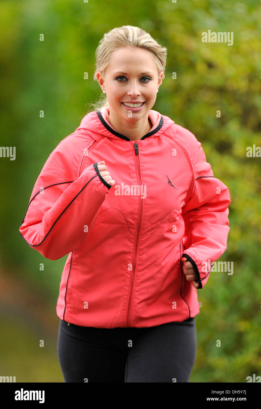 Young woman wearing a windbreaker jacket jogging, in autumn - Stock Photo