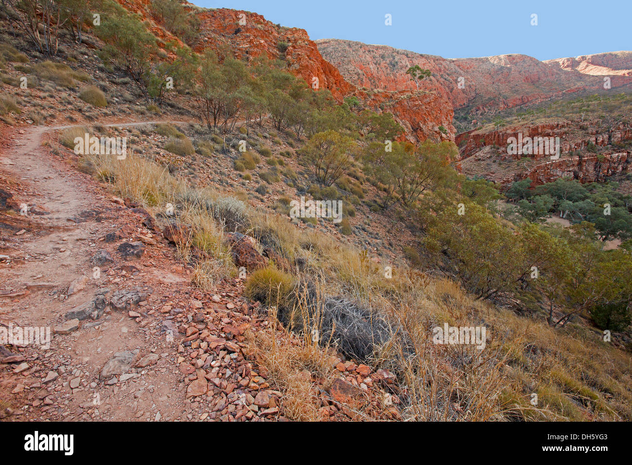 Australian outback landscape with pathway across rugged red rocky hills at Ormiston Gorge reserve near Alice Springs NT - Stock Image