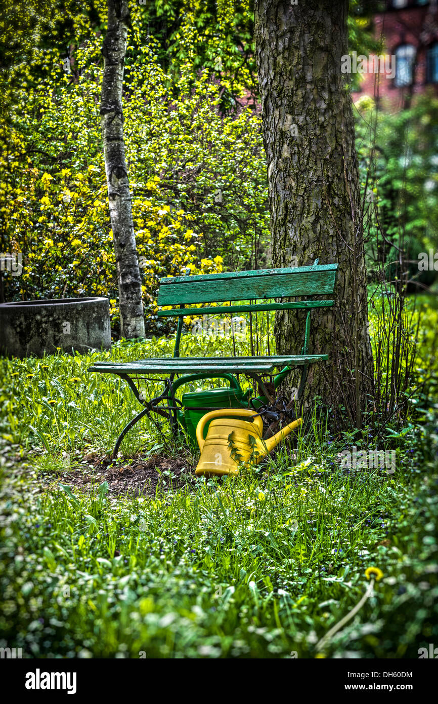 garden bench with yellow ewer. - Stock Photo