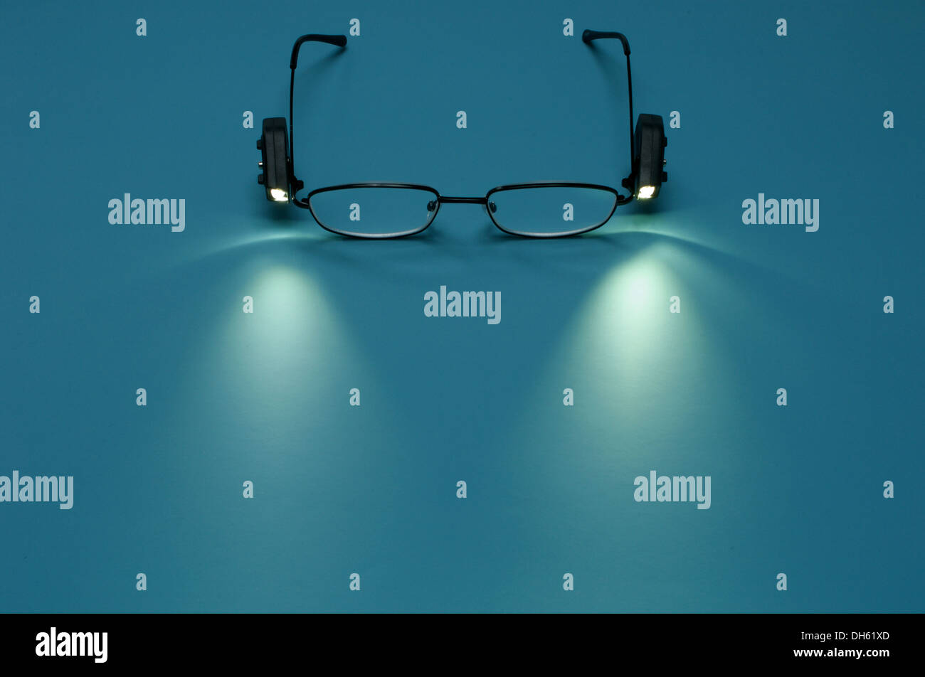 A pair of reading glasses with small attached lights - Stock Image