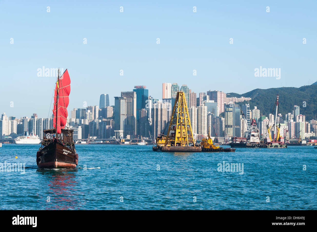 A traditional junk ship sails along Victoria Harbor in Hong Kong. - Stock Image