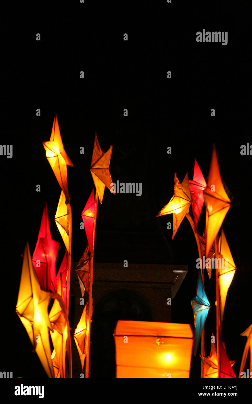 Lit up Chinese lantern stars against a night sky - Stock Image
