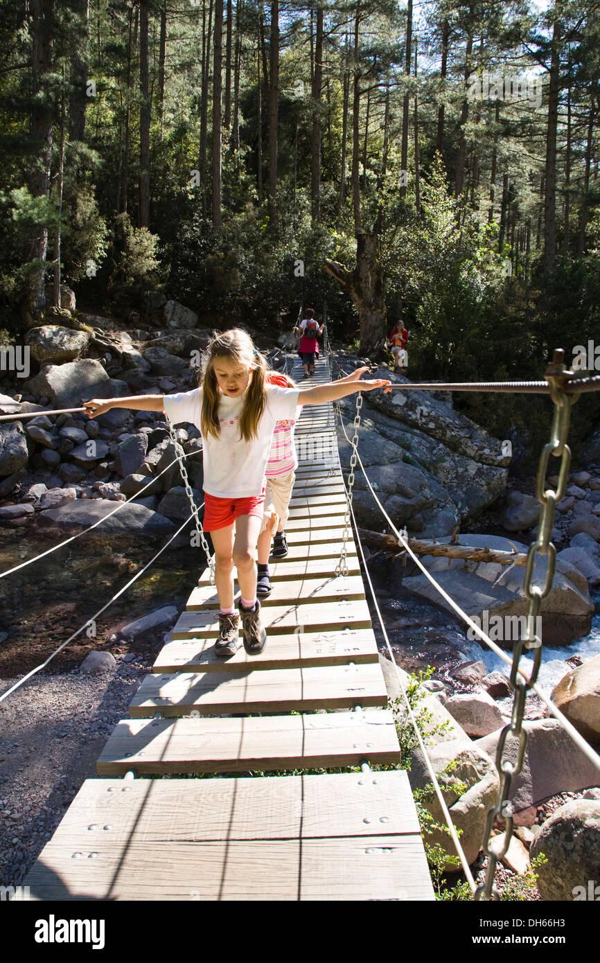 7-year-old girls on suspension bridge over Spasmiata river, Foret de Bonifatu, Corsica, France, Europe - Stock Image