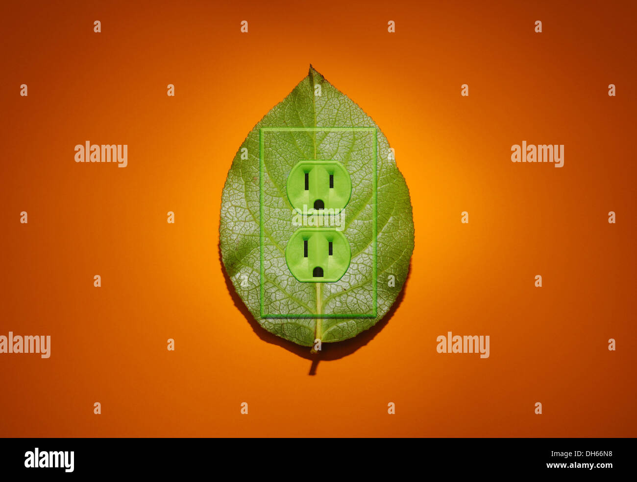 A green plant leaf with green colored electrical outlets added. Bright orange background - Stock Image