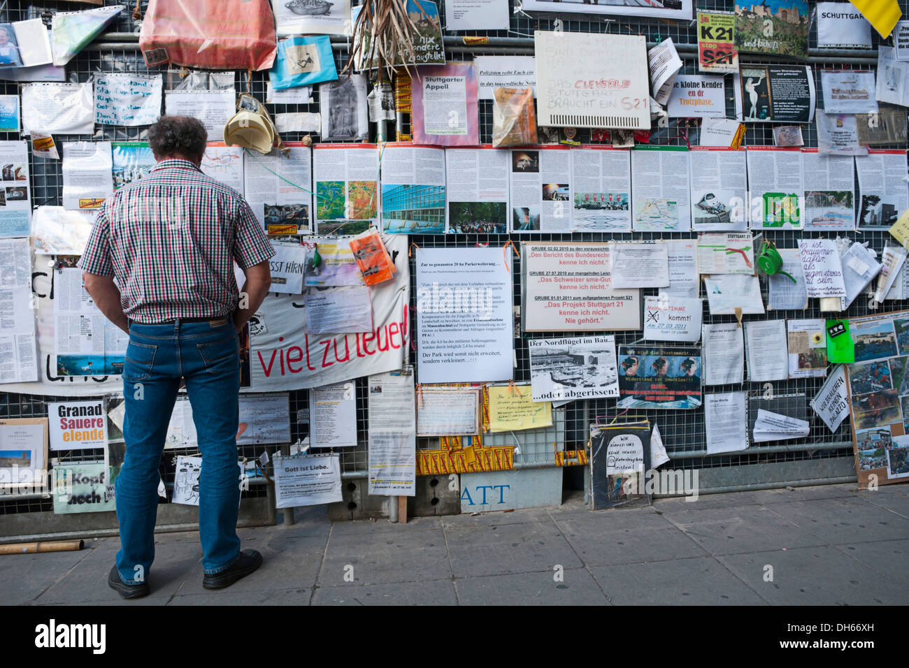 Stuttgart 21 building project, passerby and protest posters on the fence of the demolished north wing of Stuttgart - Stock Image
