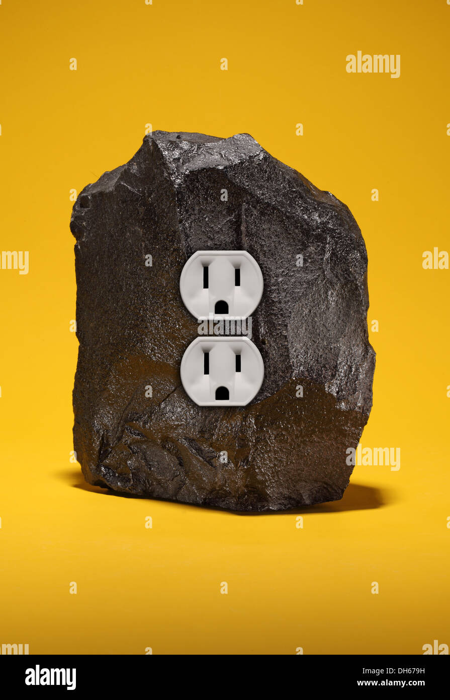 A large piece of black coal with an double electrical outlet. Bright yellow background - Stock Image