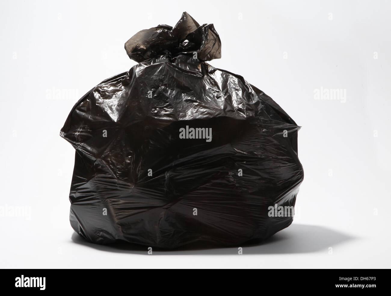 A large black filled plastic garbage bag - Stock Image