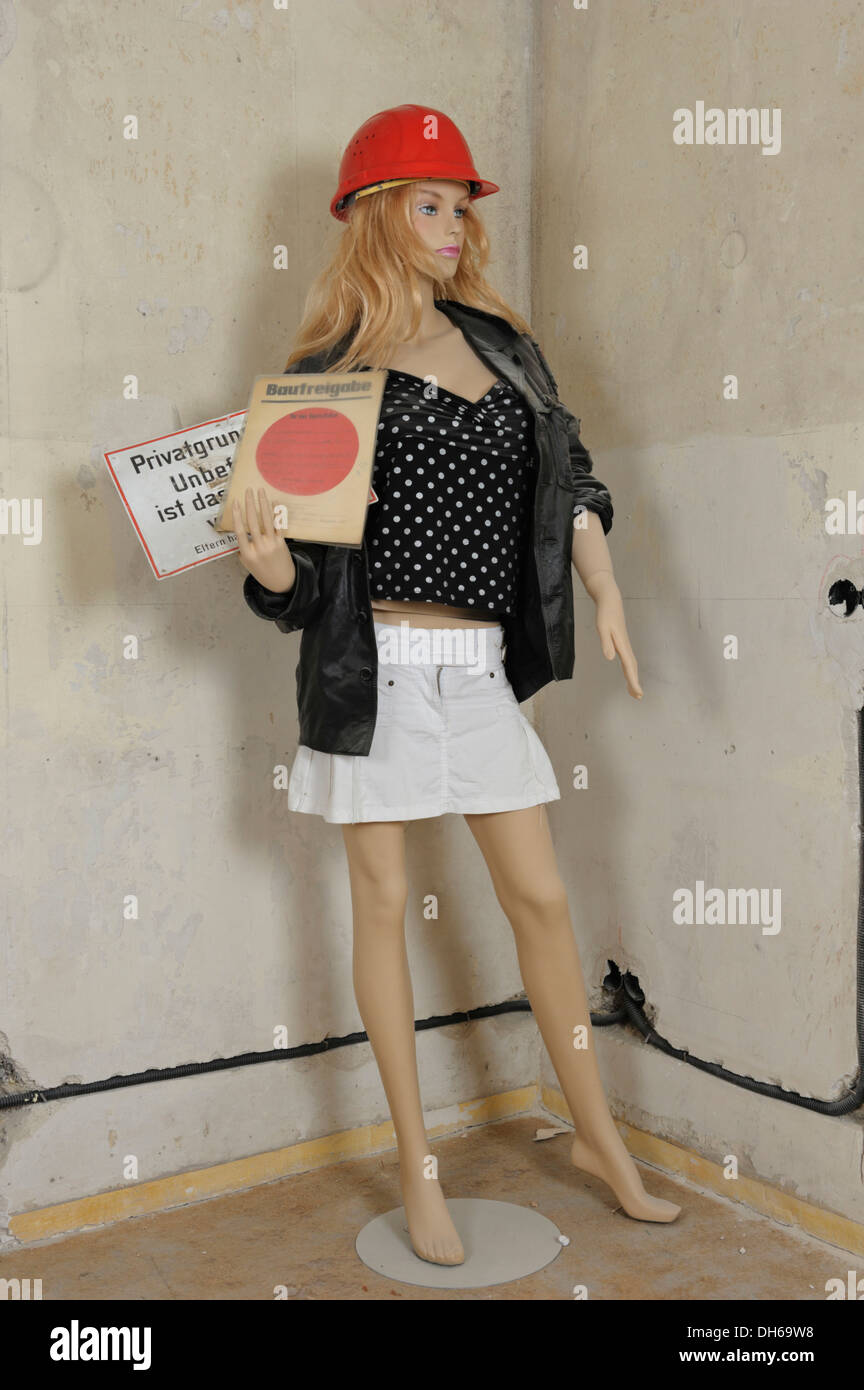 """Mannequin with a hard hat on a building site, holding a construction approval and a """"no entry"""" sign in her hand. Stock Photo"""