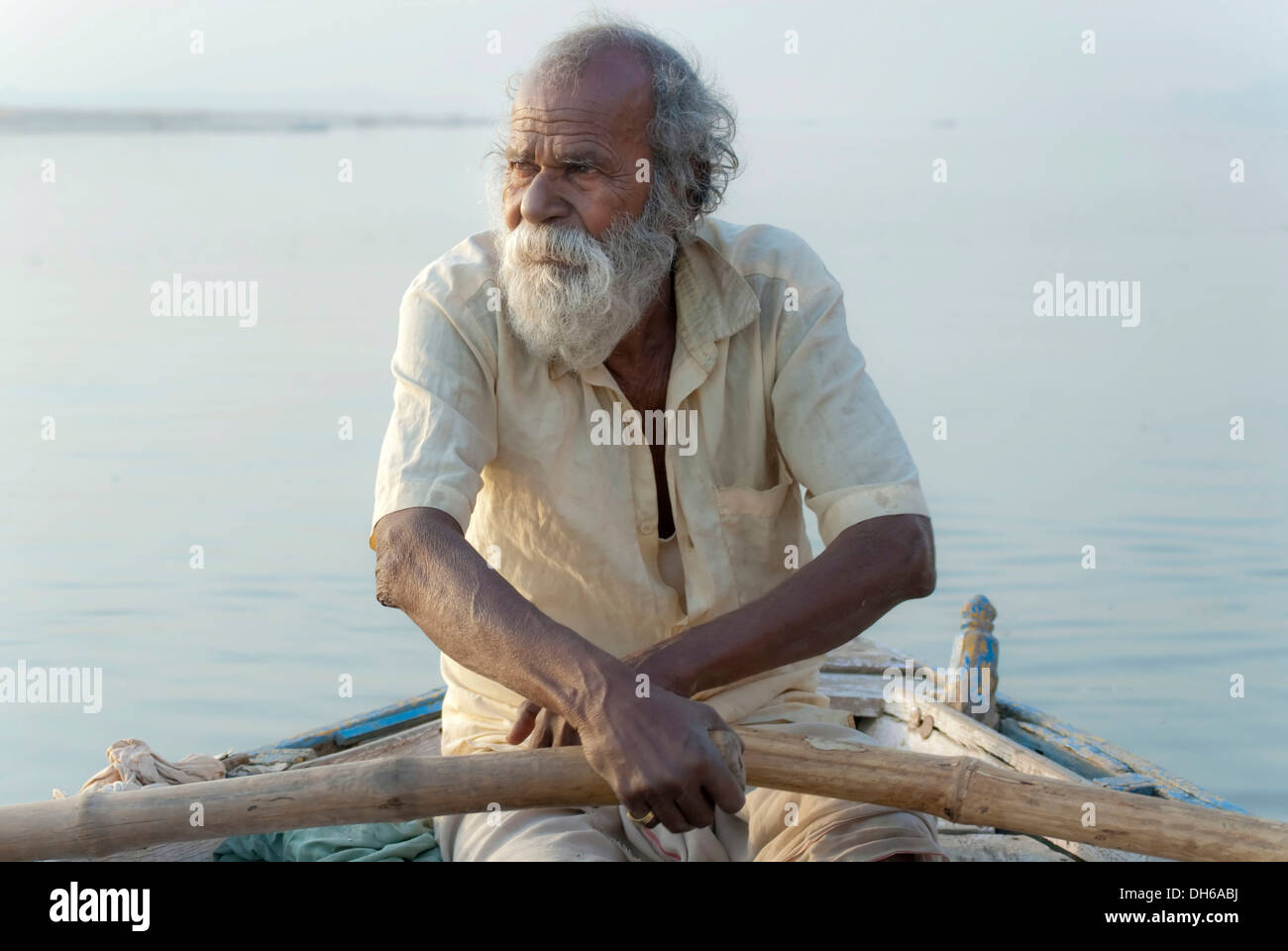 Old man rowing a boat on the Ganges river, Sunrise, Varanasi, India, Asia - Stock Image