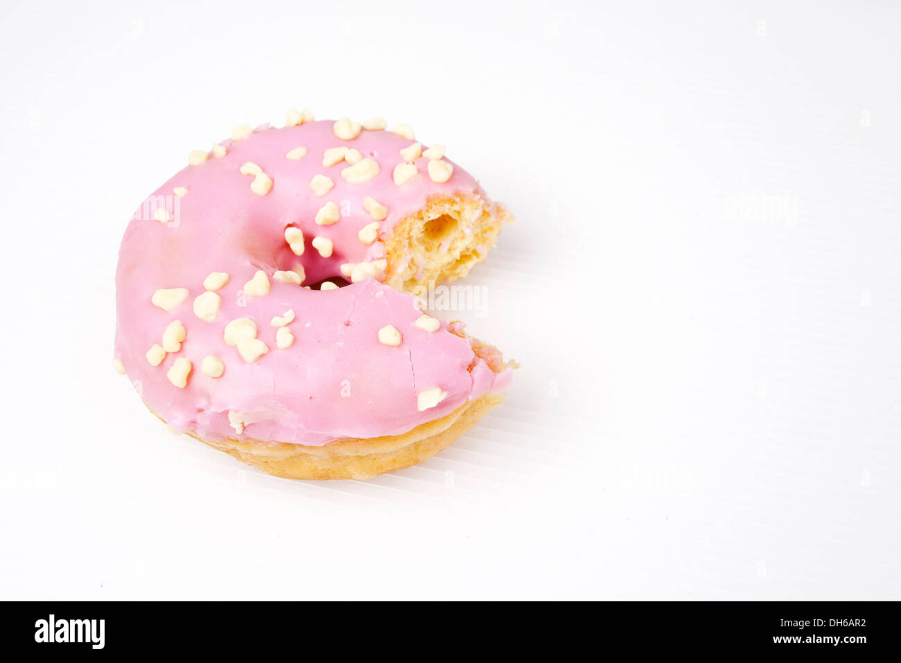 Frosted glazed Donut with chocolate sprinkles - Stock Image