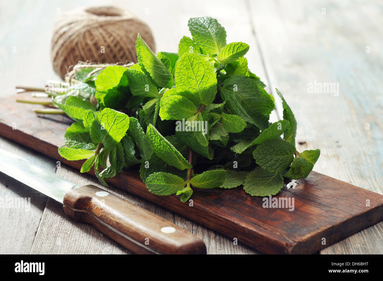 Green mint leaves with lime on wooden background - Stock Image