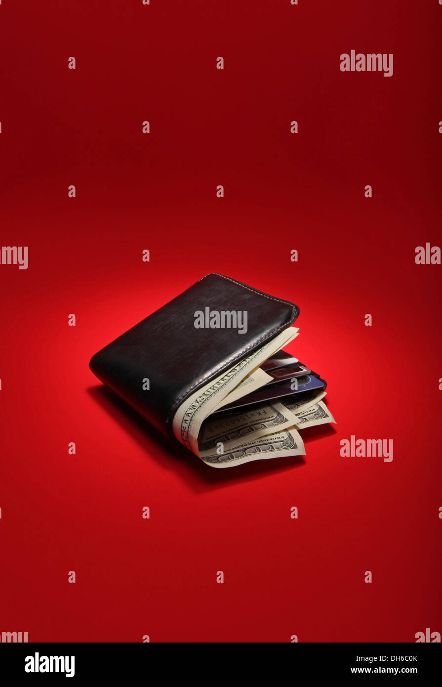 A black leather wallet filled with US currency on a bright red background - Stock Image