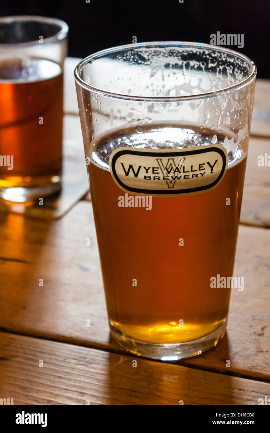 Pint of beer in a straight glass with a Wye Valley Brewery logo on a pub table. Talybont-on-Usk, Brecon, Powys, Wales, GB, UK. - Stock Image