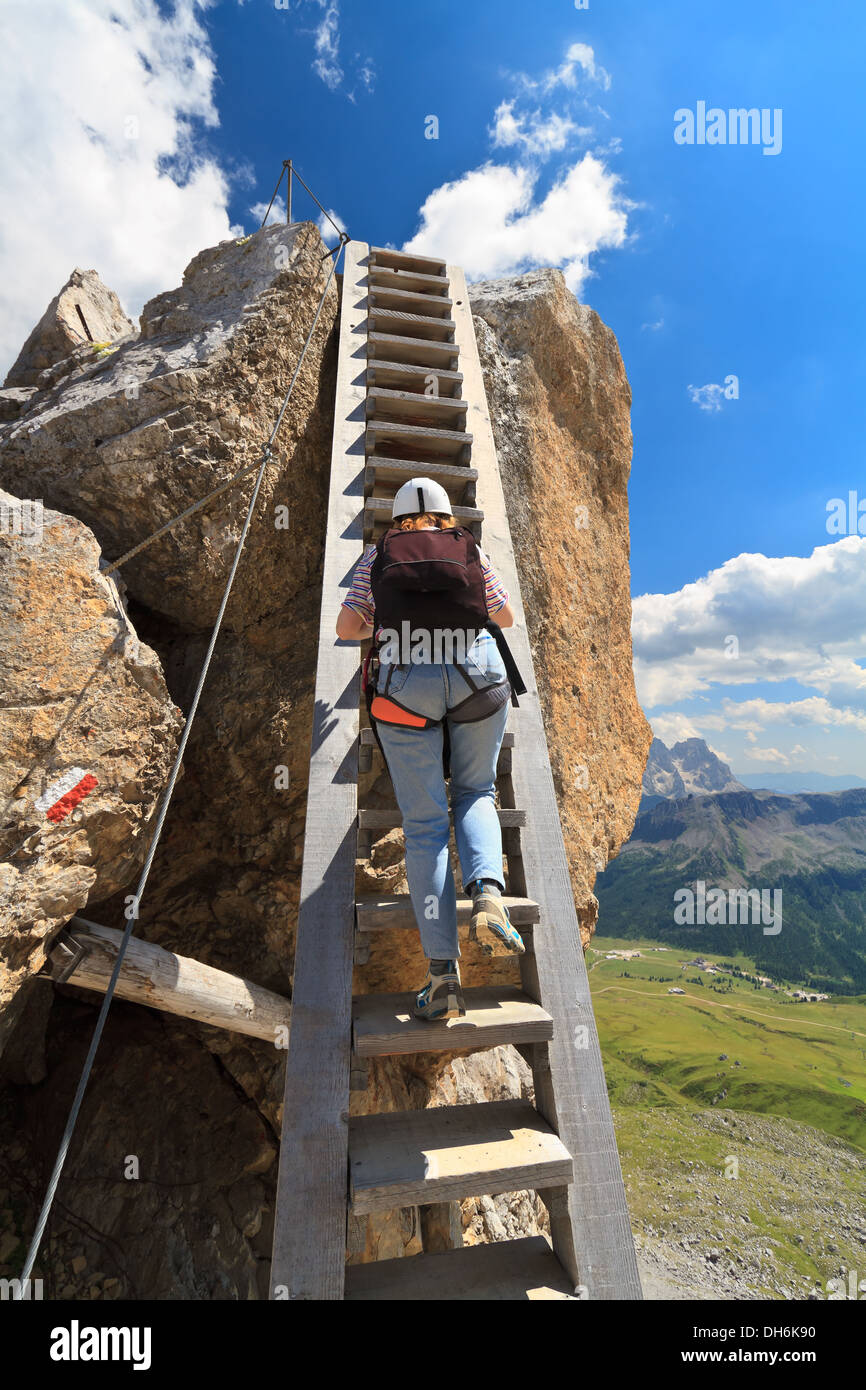 hiker on a big wooden ladder in Bepi Zac via ferrata, Trentino, Italy Stock Photo