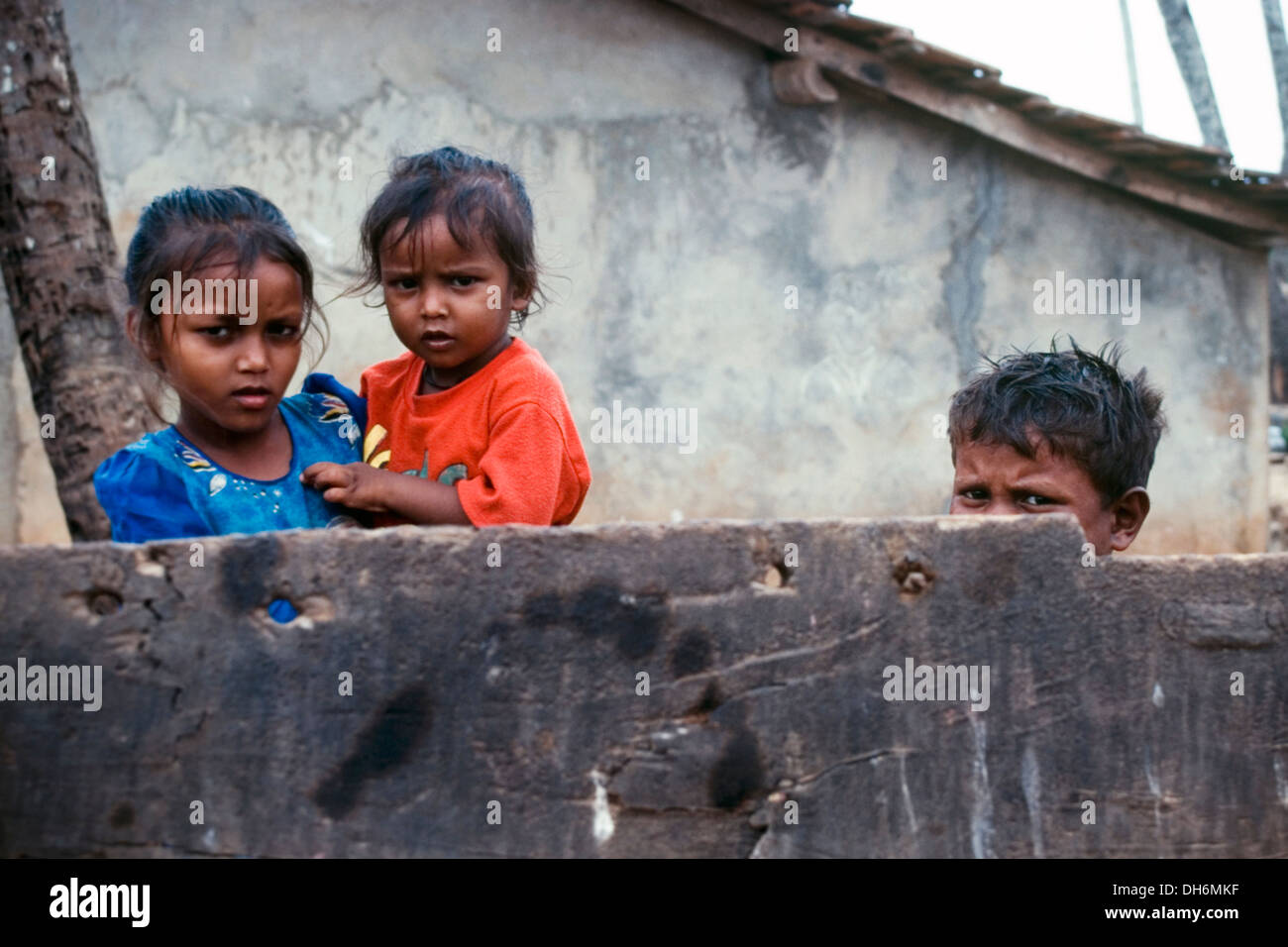 three young children standing behind a wall outside of their impoverished home in benaulim goa india - Stock Image