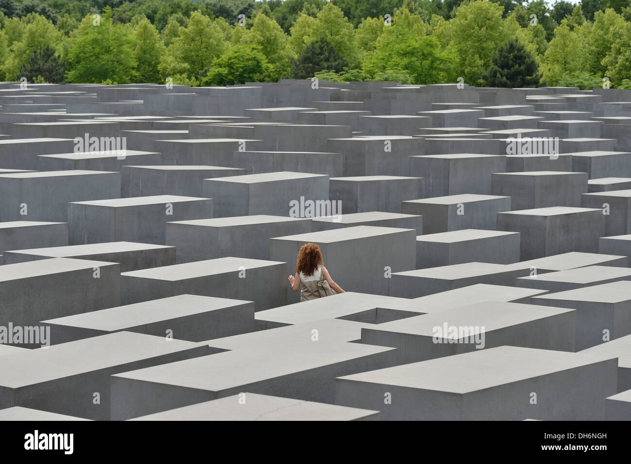 Berlin. Germany. Memorial to the Murdered Jews of Europe / Holocaust Memorial, a lone woman wanders amongst the stelae. - Stock Image