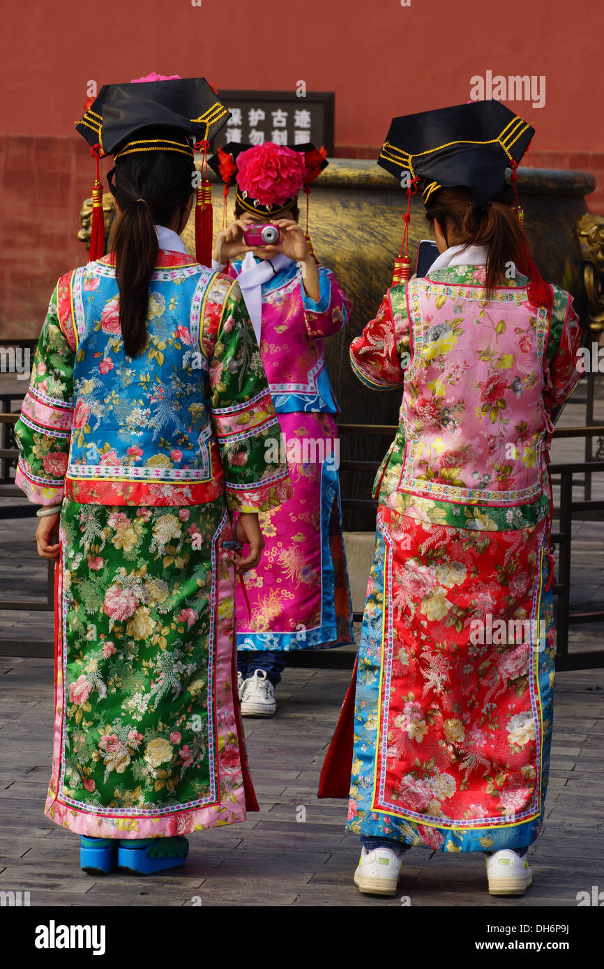 Chinese girls on a day out in the Forbidden City, Beijing, try on period