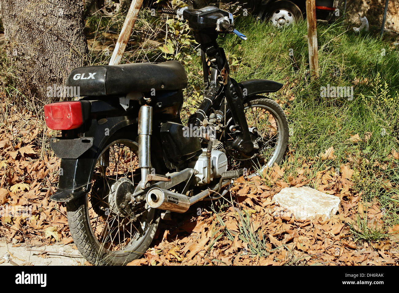 A rather dilapidated looking Honda motor cycle parked beside a road on the Greek Island of Skiathos in the Aegean Stock Photo