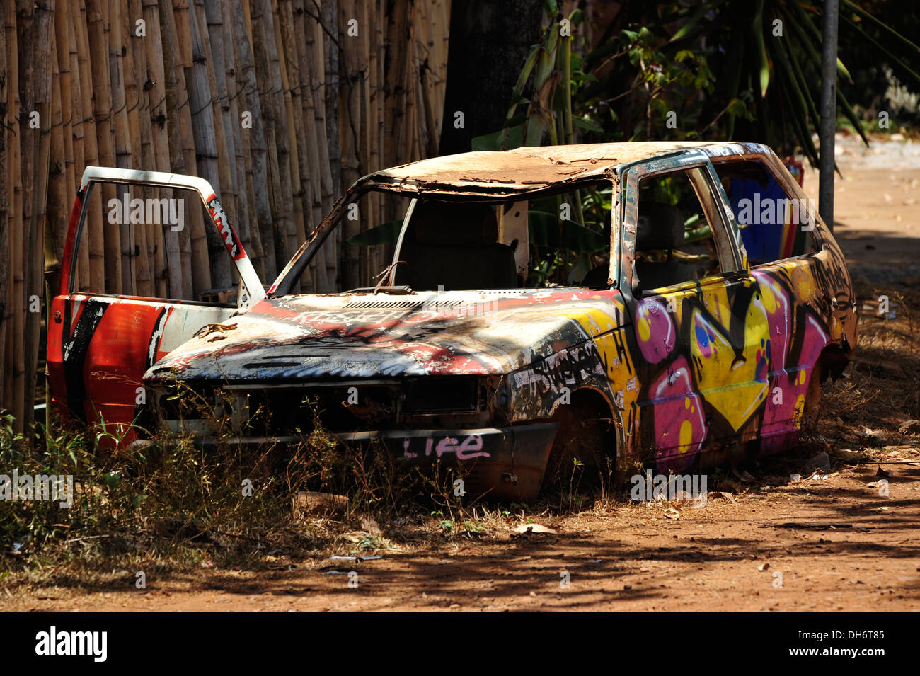 Car wreck with graffiti, Itacaré, Bahia, Brazil. - Stock Image