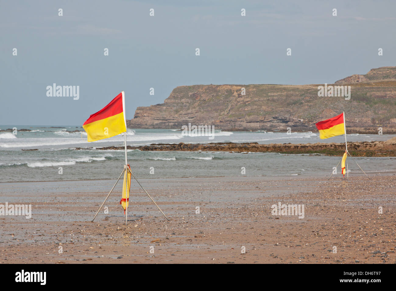 Flags indicating safe bathing and surfing areas on a Cornish beach UK - Stock Image