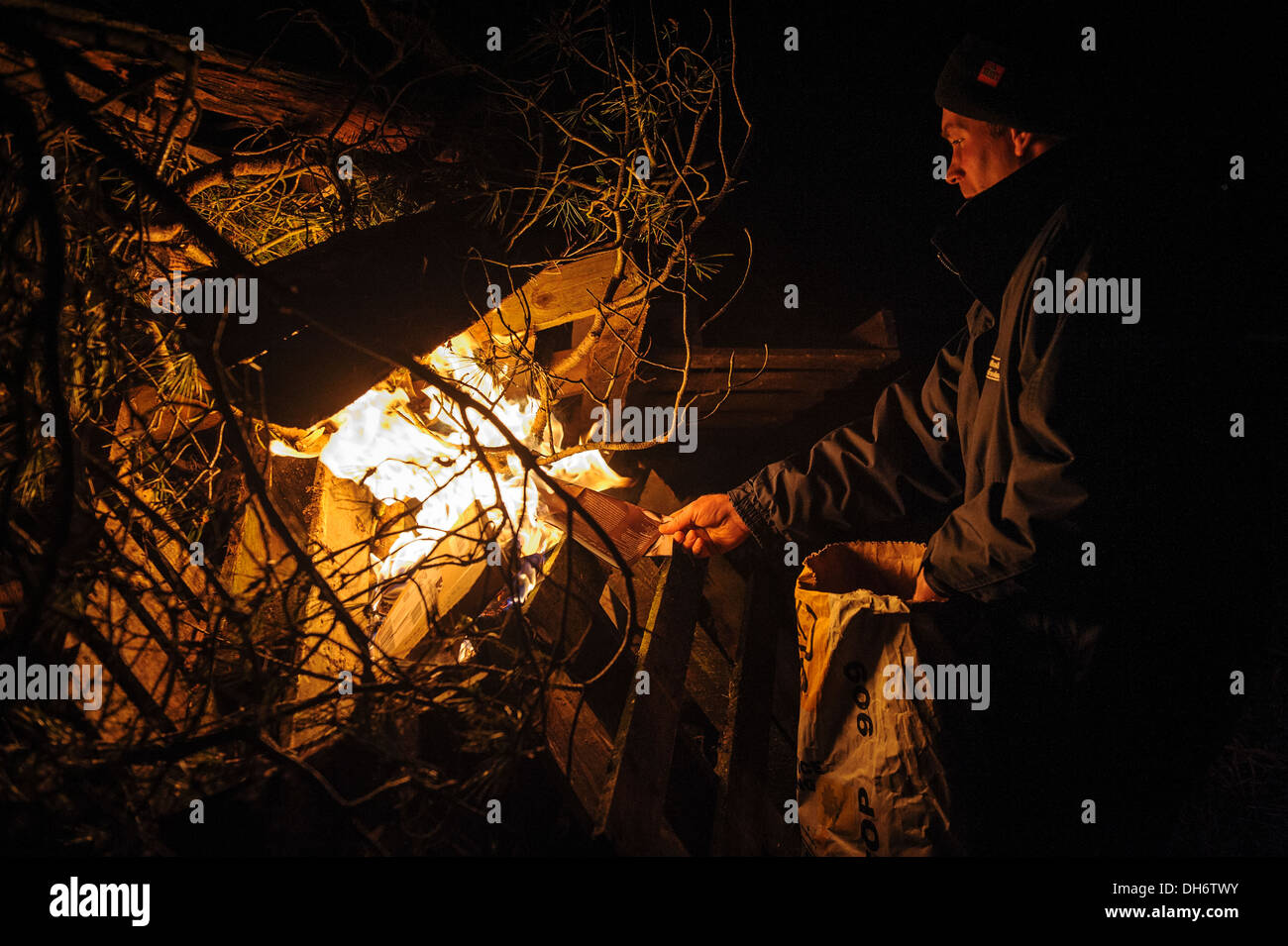 Lighting a bonfire on Guy Fawkes night - Stock Image