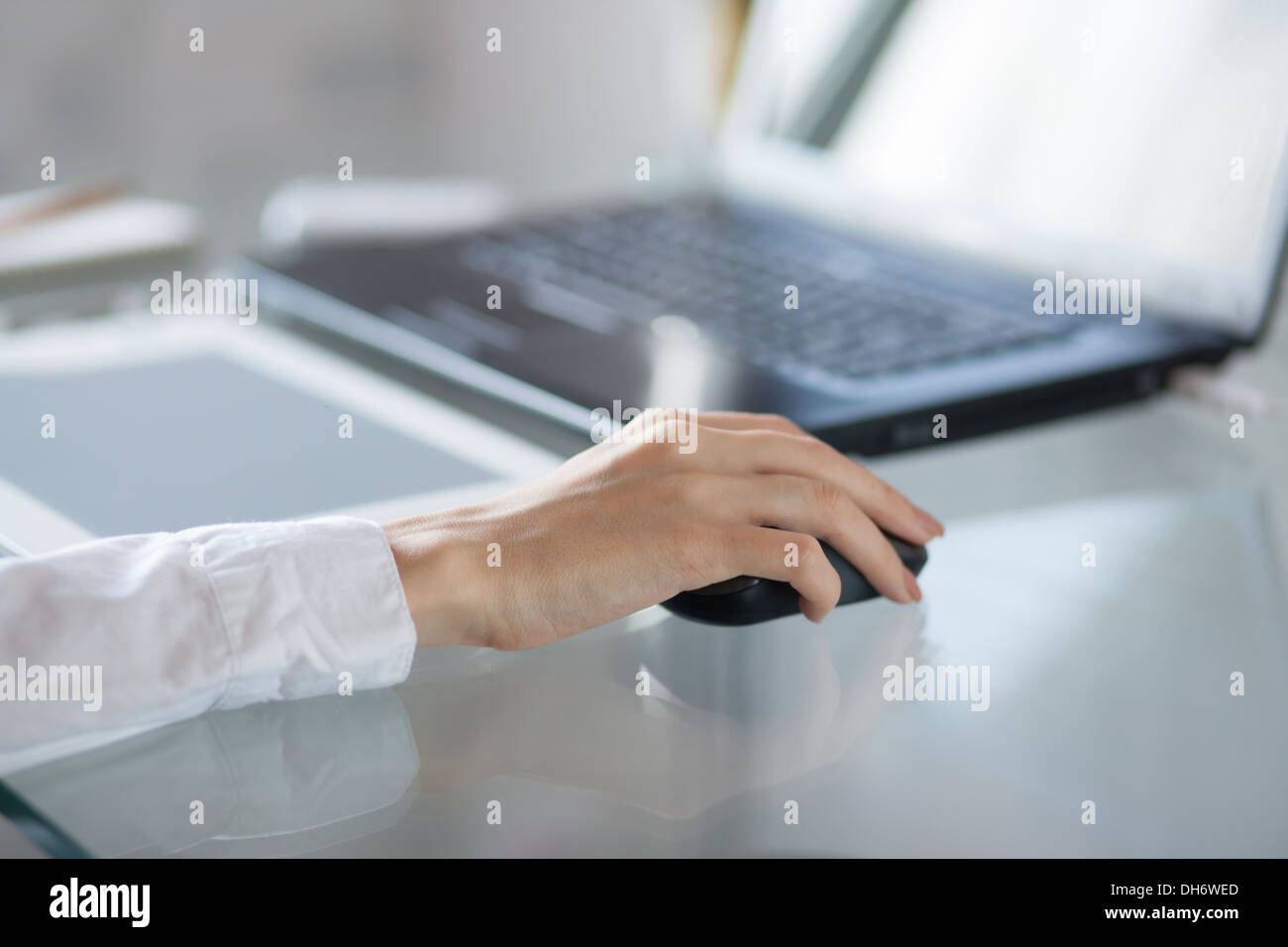 Woman's hand using cordless mouse on glass table - Stock Image